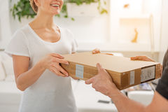 Happy laughing woman receiving parcel stock photo