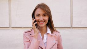 Happy laughing woman talking on mobile phone and looking in camera stock video footage