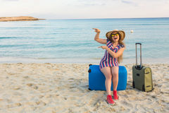 Happy laughing woman tourist with suitcases near the sea and pointing on copy space. Travel and summer vacation concepts Royalty Free Stock Images