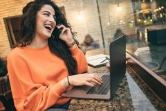 Happy laughing woman working with laptop. Friendly phone Conversations . online dating sites. Services Stock Image