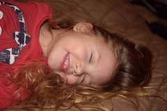 Happy laughing young girl jumping on the bed royalty free stock photos