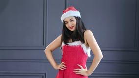 Happy laughing young girl wearing Santa Claus hat and suit dancing and having fun at studio. Medium shot. Pretty Asian Christmas woman rejoicing indoor