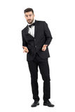 Happy laughing young luxurious man in tuxedo pointing at camera. Full body length portrait isolated over white studio background Royalty Free Stock Photos