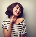 Happy laughing young short hairstyle woman in fashion blouse touching neck stock photography