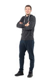 Happy laughing young sportive athlete in sweatshirt and sweatpants with crossed arms. Stock Image