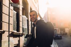 Portrait of young man laughing in sunset. Happy laughing young woman, with big natural pretty smile looks into camera in soft evening sunset light, wears urban Royalty Free Stock Image