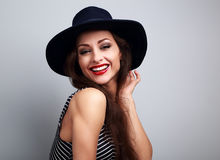 Happy laughing young woman in black hat looking on blue background stock photography