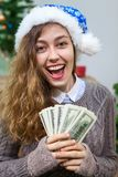 Happy and laughing young woman with cash money in hand as present at Christmas eve Stock Photography
