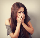 Happy laughing young woman cover two hands her mouth with fun lo Stock Image