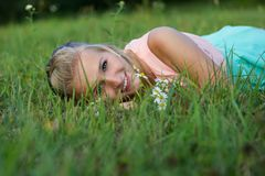 A happy laughing young woman laying on the grass Royalty Free Stock Image