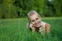 A happy laughing young woman laying on the grass Stock Images
