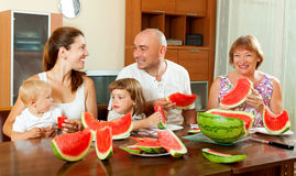 Happy laughting family having watermelon behind the table Royalty Free Stock Photo