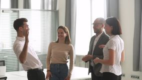 Happy leader motivate diverse employees business team give high five. Together, excited office workers group and coach engaged in teambuilding celebrate success stock footage