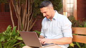 Happy lecturer sitting on bench using laptop Royalty Free Stock Photos