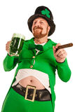 Happy Leprechaun with green beer. Photo of a man in a Leprechaun costume holding green beer and smoking a cigar Royalty Free Stock Photos