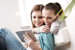 Happy lesbian couple with tablet Stock Images