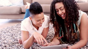 Happy lesbian couple using laptop laying on carpet. In slow motion stock video