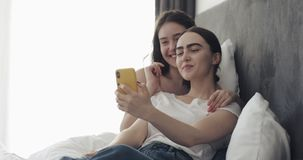 Happy lesbian couple video chatting on smartphone lying in the bed at home. They showing engagement rings enjoying. Romantic celebration. LGBT lesbian couple stock video