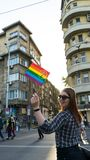 Happy Lesbian woman waving a rainbow flag in a Pride parade, Sofia Pride Festival in the street. Red head sunglasses proud. Rights, gay, bisexual, freedom royalty free stock photography