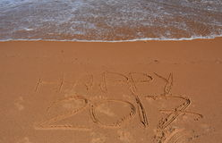 Happy 2017 lettering on the beach. Happy 2017 written on sand at sunset. Happy 2017 lettering on the beach. `Happy 2017` drawn on sand on a beach, closeup shot Royalty Free Stock Photo