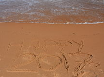 Happy 2017 lettering on the beach. Happy 2017 written on sand at sunset. Happy 2017 lettering on the beach. `Happy 2017` drawn on sand on a beach, closeup shot Royalty Free Stock Images