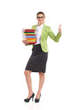 Happy librarian showing thumb up. Elegance woman in green suit jacket, black skirt and glasses holding a stack books and showing thumb up. Full length studio Stock Images