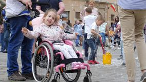 Happy life of children with disabilities, little girl in wheelchair is rejoices with soap bubbles on open air