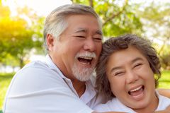 Happy life and long lived concept. Attractive handsome old man and charming beautiful old woman are laughing funny stories royalty free stock photos