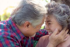 Happy life and long lived concept. Attractive handsome old man and charming beautiful old woman staying together and he telling royalty free stock images