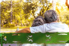 Happy life and long lived concept. At the end of life, older couple sitting together on bench at a park. Grandfather or older royalty free stock photo