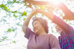 Happy life and long lived concept. Old woman of wife dancing with her husband or old man at park under tree. Grandmother and royalty free stock photo