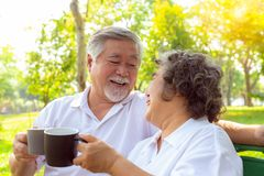 Happy life and long lived concept. Older couple is clinking cup of coffee and enjoying the drink in the morning. Handsome stock photo