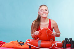 Happy lifeguard woman lying on rescue ring buoy. Stock Photo