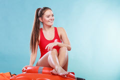 Happy lifeguard woman sitting on rescue ring buoy. Royalty Free Stock Image