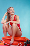 Happy lifeguard woman sitting on rescue ring buoy. Stock Image