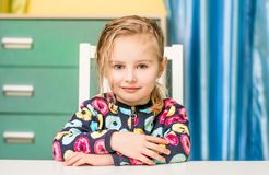 Happy liitle girl sitting at the table stock photography