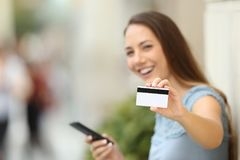 Happy on line buyer showing a credit card. To the camera on the street Royalty Free Stock Photography
