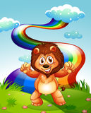 Happy lion at the hilltop with rainbow in the sky Royalty Free Stock Photo