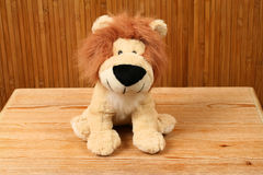 Happy lion king. Plush lion mascot on wooden background. Cheerful animals king Royalty Free Stock Photos