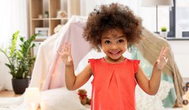 Happy little african american girl at home. Childhood and people concept - happy little african american girl over kids tent or teepee at home background royalty free stock images
