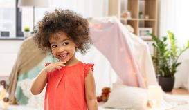 Happy little african american girl at home. Childhood and people concept - happy little african american girl over kids tent or teepee at home background stock photo