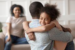 Happy little african kid daughter embracing black dad at home. Happy cute little african american kid daughter embracing black dad at home, funny small mixed royalty free stock images