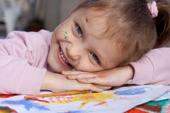 Happy little artist. Portrait of a smiling little girl with her painting Royalty Free Stock Photos