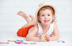 Happy little artist girl in a hat draws pencil Stock Photos