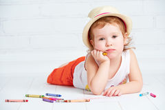 Happy little artist  girl in a hat draws pencil Stock Photo