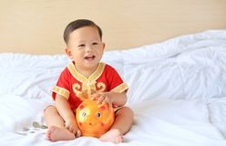 Happy little Asian baby boy in traditional Chinese dress with a piggy bank sitting on bed at home. Kid saving money concept.  stock image