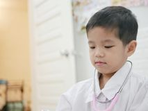 Happy little Asian baby getting dressed as a doctor stock image