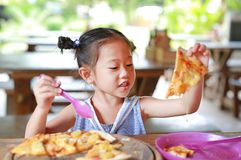 Happy little Asian child eating pizza on the table stock image