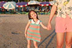 Happy little Asian child girl holding mother hands on beach while evening sunlight stock images