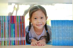 Happy little Asian child girl lying on bookshelf at library. Children creativity and imagination concept royalty free stock photography
